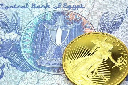 A macro image of a green and yellow fifty piastre note from Egypt with a gold coin.  Shot close up.