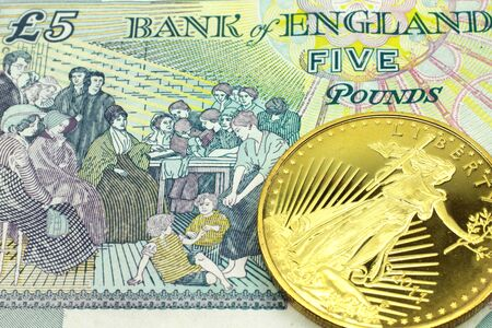 A macro image of a colorful five pound note from the UK with a gold coin.  Shot close up.