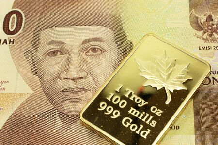 A macro image of a orange 5000 rupiah bank note from Indonesia with a gold bar.  Shot close up. Stock Photo