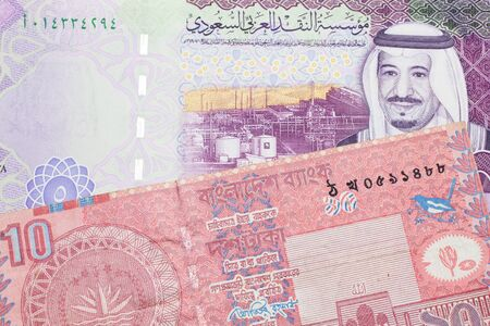 A red ten taka note from Bangladesh, close up in macro with a five Saudi riyal note