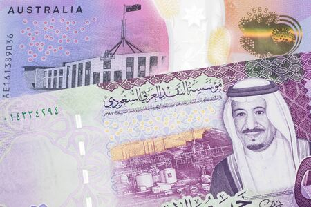 A close up image of a purple, five Australian dollar note close up, in macro with a five riyal note from Saudi Arabia