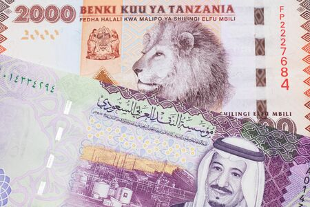 An orange and white two thousand Tanzanian shilling note with a colorful five riyal note from Saudi Arabia in macro