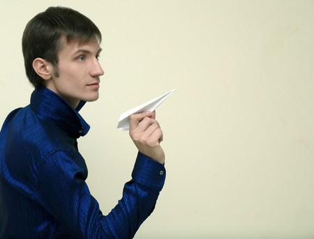 a young man is going to start to fly a paper airplane     photo