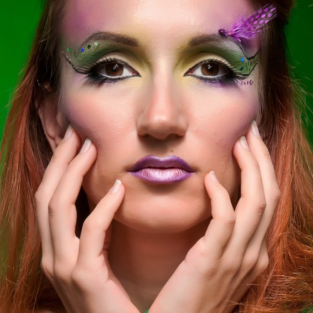Beautiful fashionable festive colorful makeup with purple feather photo
