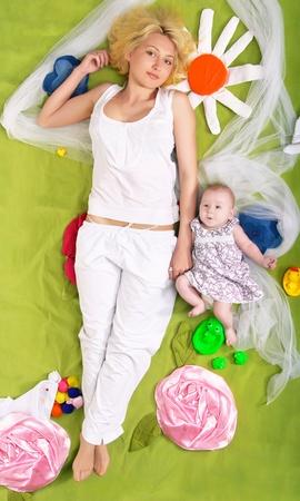developmental: A young mother and her little daughter lie full-length on developmental mat