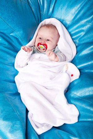 swaddling: A baby wrapped up in the white swaddling band with the red dummy