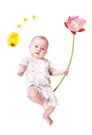 A baby with a big flower and some toy ducks