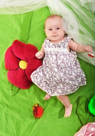 A smiling baby lies full-length near the artificial flower Stock Photo - 9748909