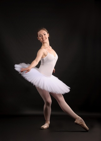 Ballerina in a white skirt and a bathing suit, pointe, dance poses