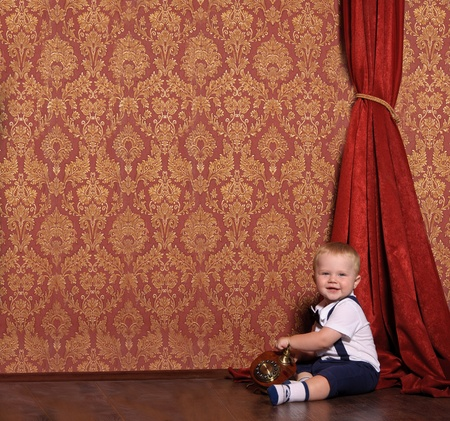 little child in a suit sitting in an vintage interior with the phone in his hand photo