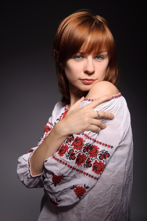 beautiful red-haired girl with blue eyes wearing ukrainian national cross-stitched costume photo