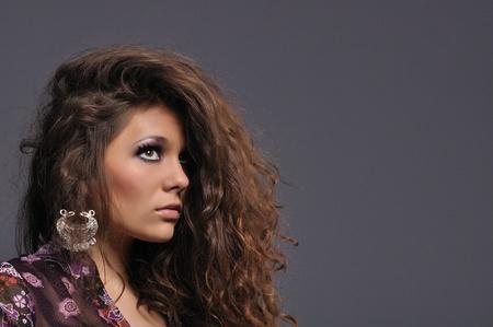 sexy brunette girl with wavy long hair wearing oriental silver earrings Stock Photo - 10291585