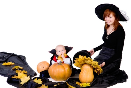 little halloween baby boy playing with mother witch near pumpkings among yellow leaves and smiling photo