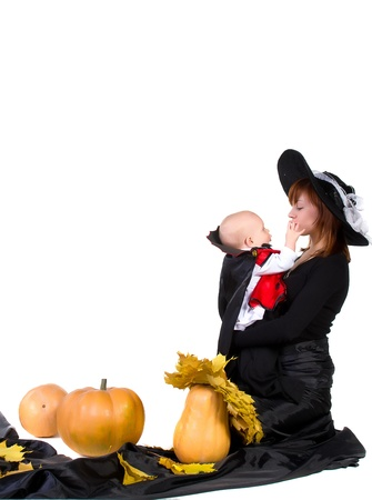 little halloween baby boy playing with mother witch near pumpkings among yellow leaves photo
