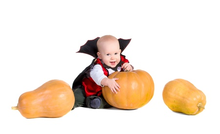little baby boy in black halloween cloak playing with pumpkins and smiling