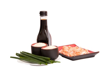 appetizing sliced salmon in rectangulat dish, bottle of soya sauce, boiled rice in drinking bowl and green leek isolated on white background photo
