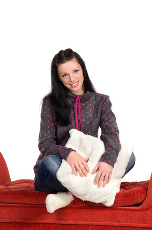 girl sitting on a red pufe, hugging a white cushion photo