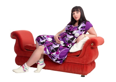 Pregnant woman sitting on a red couch in a bathrobe photo