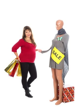 nice pregnant woman chooses dress with butterfly brooch for sale  Stock Photo
