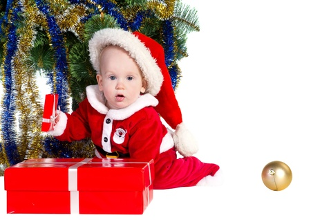 little baby boy wearing Santa's costume sitting and holding a box with christmas 