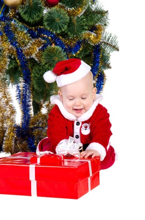 little baby boy wearing Santas costume sitting and holding a box with christmas  presents photo