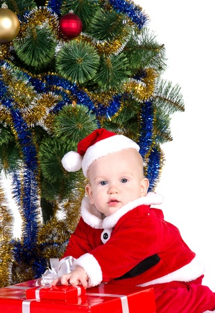 little baby boy wearing Santa's costume sitting and holding a box with christmas  presents photo
