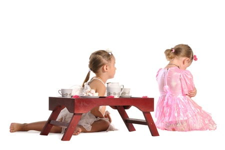 two pretty twins sisters in beautiful dresses having tea wtih zephyr sitting at coffee table  isolated on white background Stock Photo - 11885035