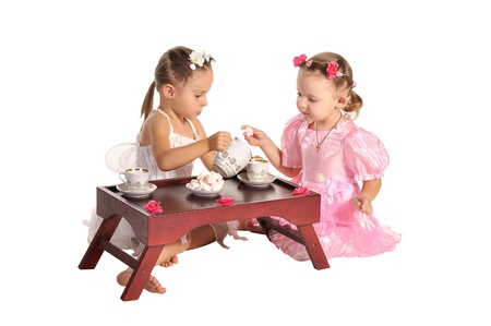 two pretty twins sisters in beautiful dresses having tea wtih zephyr sitting at coffee table  isolated on white background