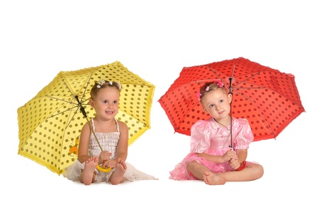 two little barefooted  twins sisters in beautiful dresses sitting with spotted red and yellow umbrellas isolated on white background photo