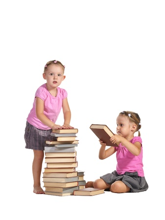 two nice little barefooted twins girls sitting at the stacks of books and reading isolated on white background photo
