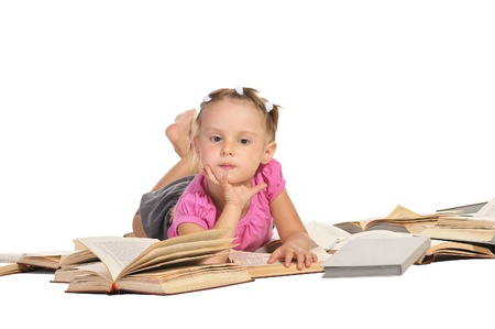 nice little barefooted girl lying on the pile of open of books and smiling isolated on white background Stock Photo - 11885031