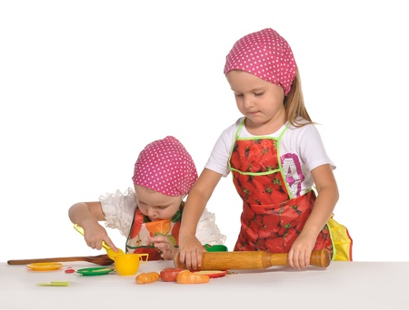two pretty little twins sisters wearing spotted pink headscarfs and colourful aprons pretending housewifes cooking isolated on white background
