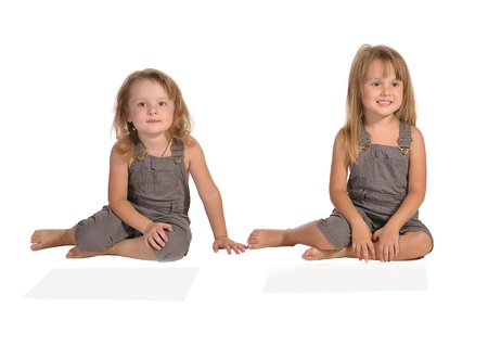 rompers: dos hermanas gemelas bonitas sentado en el suelo descalzo y vistiendo mamelucos aisladas sobre fondo blanco Foto de archivo