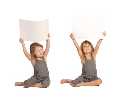 barefooted: two pretty barefooted twins sisters in rompers holding blank paper sheets above their heads isolated on white background Stock Photo