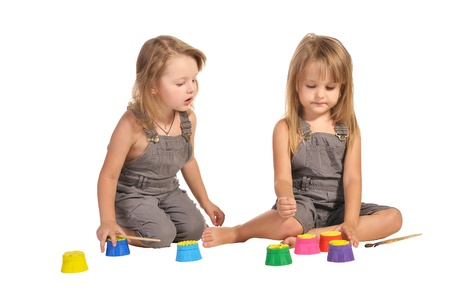 rompers: dos hermanas gemelas muy descalzos en la elecci�n de las pinturas peleles aisladas sobre fondo blanco