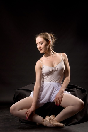 Ballerina in a white skirt and a bathing suit, pointe, dance poses photo