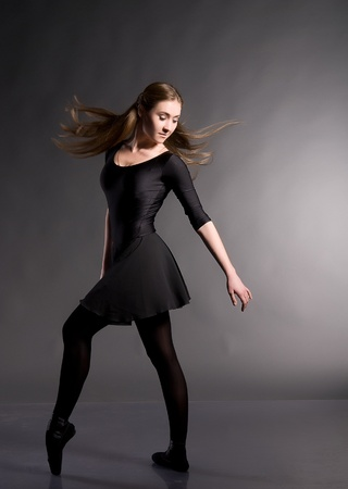 Ballerina in a black skirt and a bathing suit, pointe, dance poses