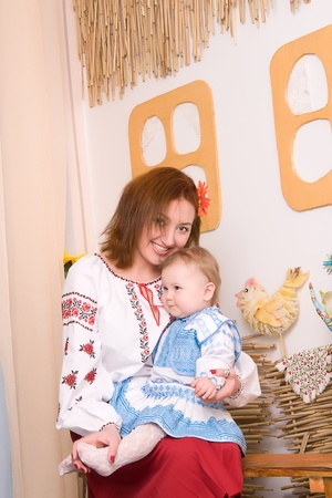 Mother and child sits on the bench in the Ukrainian national costumes photo