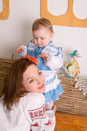 daughter playing with a flower in her mothers head. In the Ukrainian national costumes photo