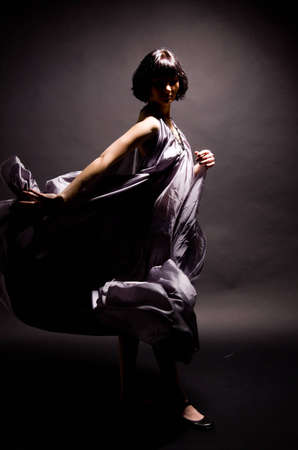 girl in a gray dress flying on a black background photo
