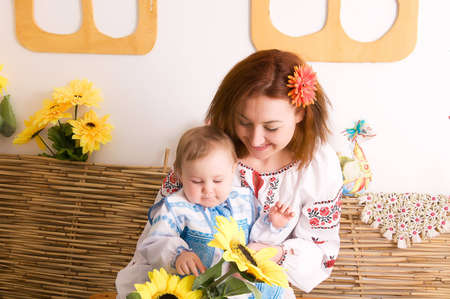 Mother playing with her little daughter. In the Ukrainian national costumes photo