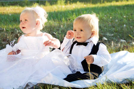 Children dressed as bride and groom play with each other photo