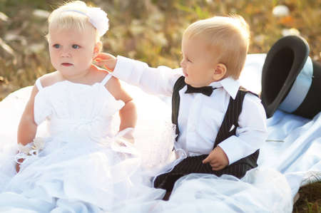 Children dressed as bride and groom play with each other Stock Photo