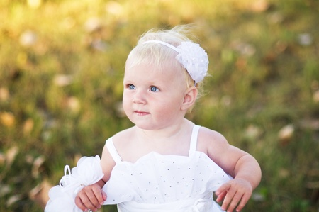 little girl in a white wedding dress is on the grass Stock Photo