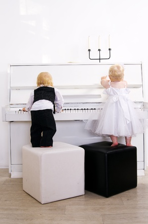 boy and girl playing in a concert dress on a white piano