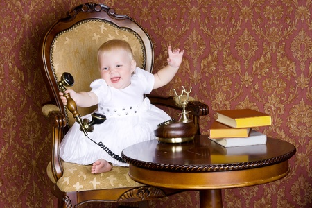 Laughing girl with the phone in his hand sitting on an old chair Stock Photo