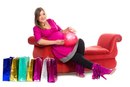 pregnant women in pink color dresses, with shopping bags on white background and sofa photo
