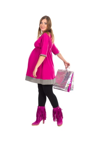Full-length beautiful pregnant woman with shopping bags, on white background  photo