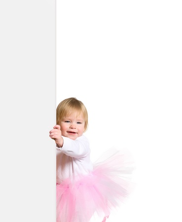 young happy smiling little girl in ballerinas tutu look outs from the blank billboard photo