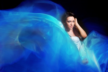 beautiful girl in the blue dress from flying fabric on a black background photo